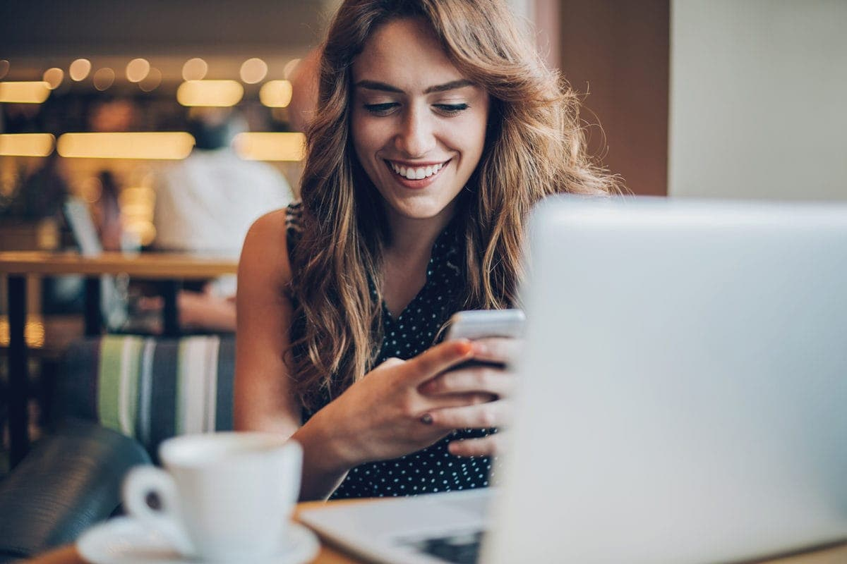 Attractive woman checks her phone in front of her laptop at a cafe